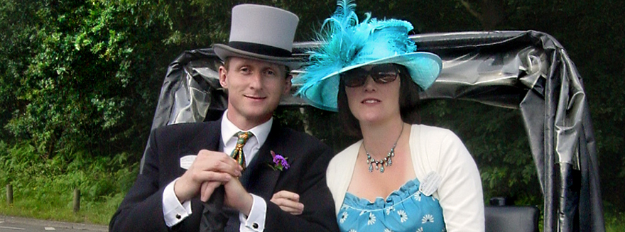 A man in a morning suit and top hat with a woman wearing a blue dress and hat are posing seated on a Bugbugs rickshaw