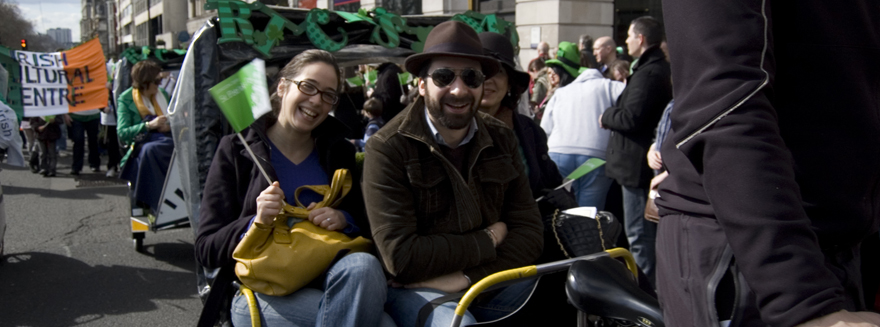 Three people seated on a rickshaw, smiling and waving a flag during an event for the Irish Cultural Centre