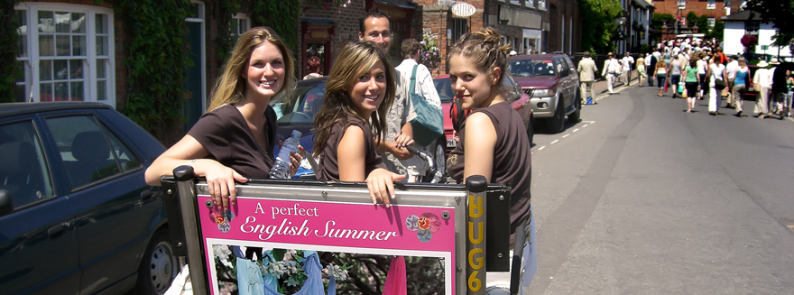 Three women posing seated on the back of a Bugbugs rickshaw on a bright sunny day