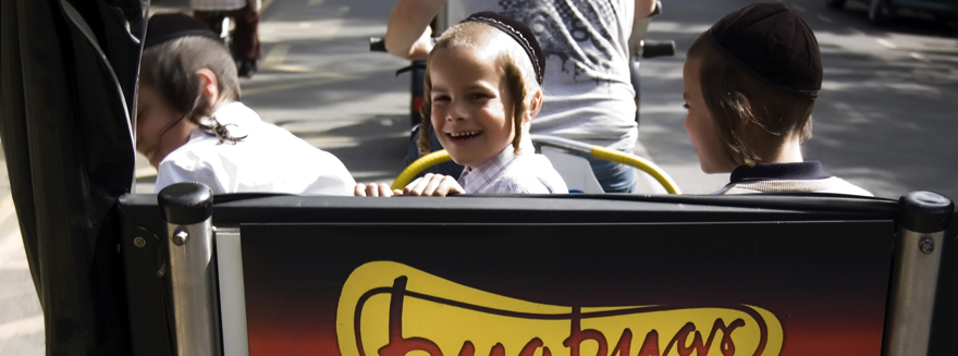 Children smiling at the back of a Bugbugs branded rickshaw