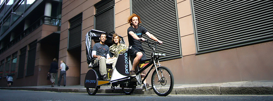 Two male passengers posing, seated at the back of a Bugbugs pedicab