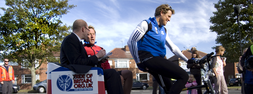 Olympic gold medalist James Cracknell pedals, while TV presenter Ben Fogle speaks to a reporter seated on the back of a Bugbugs rickshaw